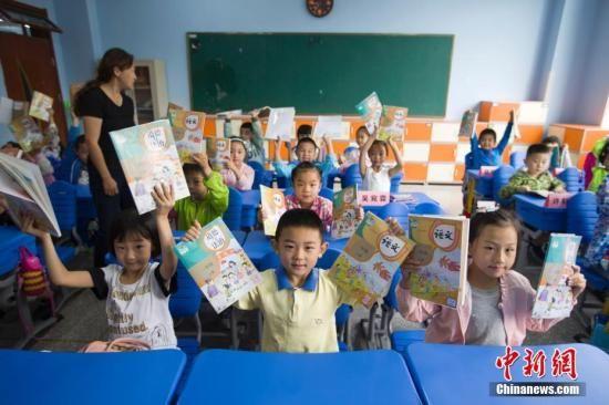 """资料图:2017年9月1日,中国教育部统一组织新编的义务教育《道德与法治》、《语文》、《历史》三科教材,在中国所有地区初始年级开始投入使用。新教材将义务教育阶段原品德课调整为""""道德与法治"""",强调德法兼修。语文教材加强了中华优秀传统文化、革命传统教育和国家主权意识教育等方面的内容设计。历史教材将社会主义核心价值观的有关内容分时期、分阶段展现。张云 摄"""
