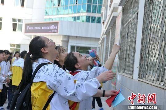 """青海师范大学附属中学的高三学生们守候纸飞机""""祝福""""降落。 央姬卓玛 摄"""