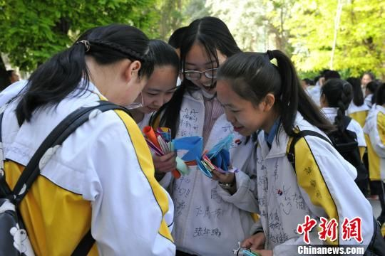 """青海师范大学附属中学的高三学生们彼此分享收到的纸飞机""""祝福""""。 央姬卓玛 摄"""