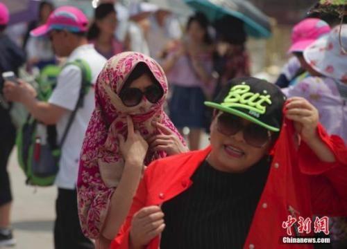 5月25日,北京炎热高温天气持续,天安门前游客纷纷用纱巾和衣服护住头部防晒。 中新社记者 贾天勇 摄