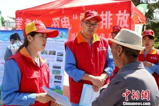 图为环保志愿者为市民讲解环保知识。 李培源 摄