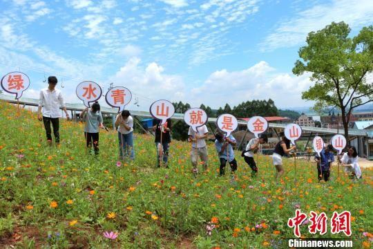 """图为学生举着写有""""青山绿水同金山银山""""的牌子。 杨孝勇 摄"""