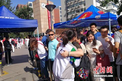 6月7日早上,一位家长在人大附中考场外与参加高考的孩子拥抱。 中新网记者 张尼 摄