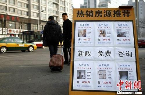 资料图:一家房产中介将广告放在十字路口处。中新社发 李慧思 摄