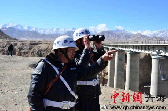 图为南山口护路中队的护路员正在查看远处的铁路 鲁丹阳摄