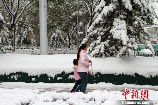 图为家长带着孩子在雪地里行走。 李培源 摄