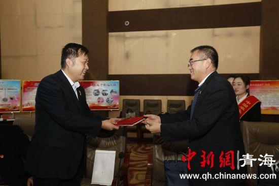 图为省分行党委委员、副行长欧阳长海(右)向王永涛颁发了农发行全国优秀党员证书