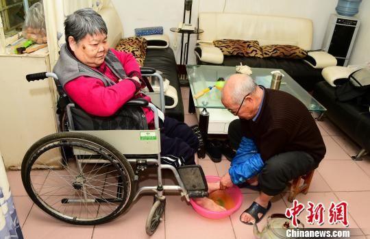 图为高虎子为偏瘫的妻子洗脚。 钟欣 摄