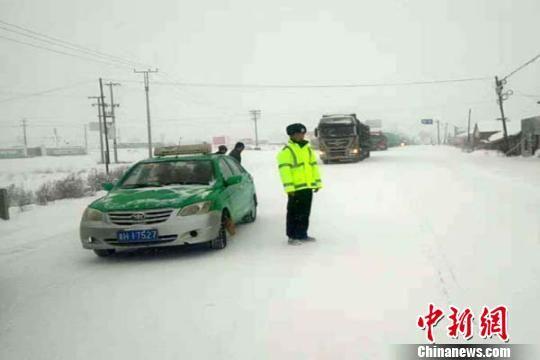 图为11月15日,降雪导致G6高速格尔木管理路段的都兰、锡铁山等收费站封闭,禁止车辆通行。交警劝停109国道前往都兰方向车辆。 张婵娟 摄