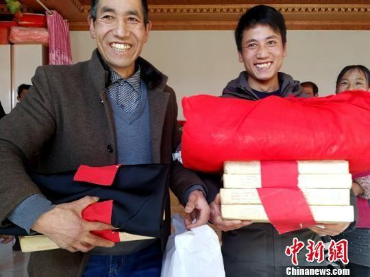 图为李吉胜(左)和小儿子准备向女方送彩礼。 张添福 摄