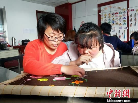 图为陈玉秀教残疾人刺绣技艺。 李隽 摄