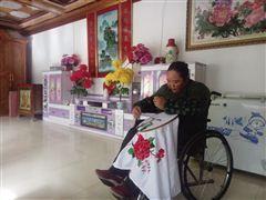 妻子李先金正在轮椅上做刺绣。