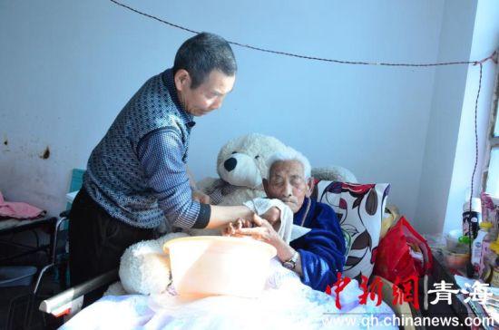 图为女婿张学芝帮98岁的岳父擦洗脸颊和双手准备吃饭。鲁丹阳摄