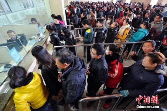 资料图:旅客在火车站购票。中新社发 韦亮 摄