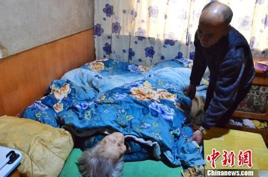 图为儿子李海明照顾母亲唐秀兰。 鲁丹阳 摄