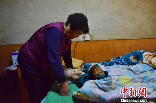 图为女儿李玉华照顾母亲唐秀兰。 鲁丹阳 摄