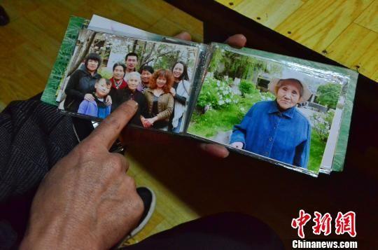 图为儿子李海明翻看母亲唐秀兰的照片。 鲁丹阳 摄