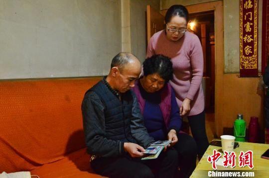 图为儿子李海明、女儿李玉华和外孙女谢占香一起翻看唐秀兰的照片。 鲁丹阳 摄