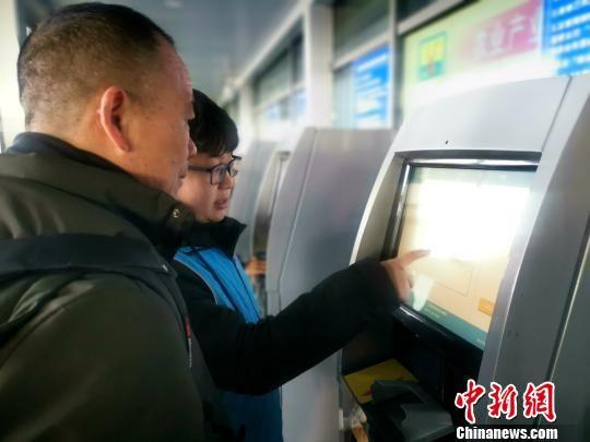 图为志愿者为旅客进行取票服务。 李隽 摄