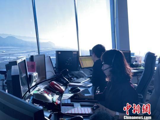 """图为塔台管制室内,管制员正在""""指挥""""飞机。 孙睿 摄"""