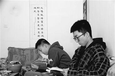豆弘远(右一)春节回家,仍保持着每天读书的好习惯。摄影:姚斌