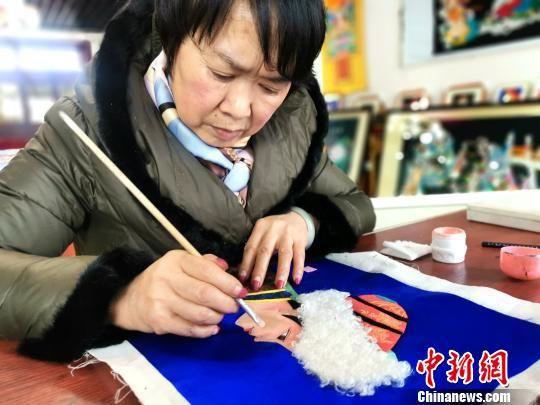 图为乔应菊正在为堆绣作品上色。 李隽 摄
