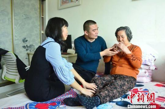 图为李明君和妻子王勤君正在照顾母亲李得花。 鲁丹阳 摄