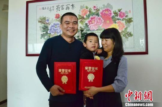图为李明君和妻子王勤君抱着小儿子。 鲁丹阳 摄