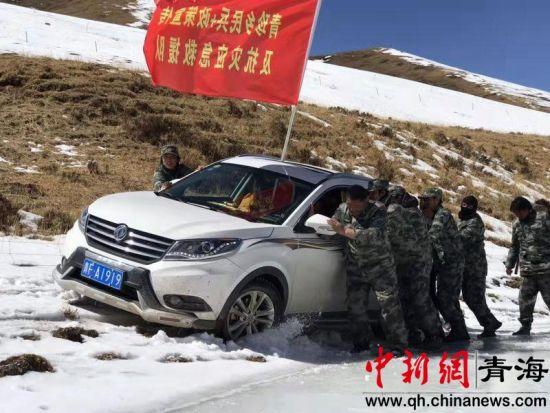 图为武警官兵在雪地里推车。