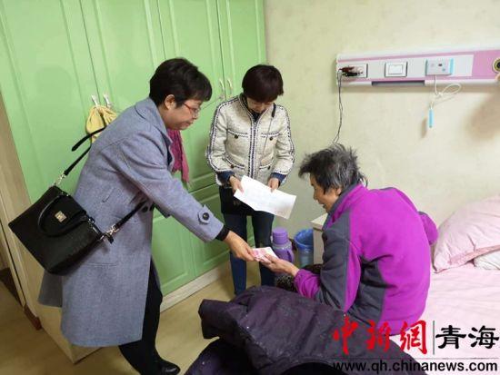 图为南山西社区为患病母女俩送去帮扶金。钟欣摄