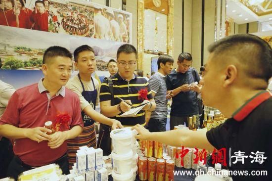 图为川商正在了解黄南当地特色产品