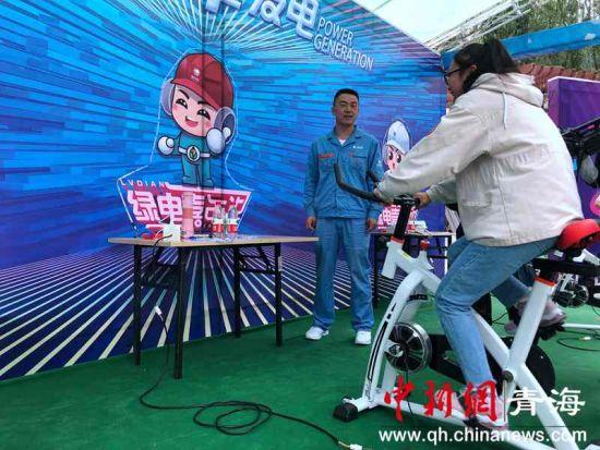 """图为青海西宁民众体验""""榨汁单车""""。罗云鹏摄。"""