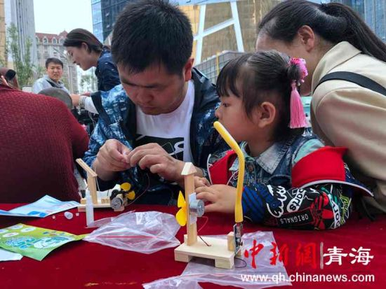 图为家长与孩子一起动手制作风力发电模型。罗云鹏摄。