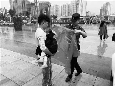 党员流动服务车工作人员为旅客怀中的孩子披上雨衣。摄影:东组
