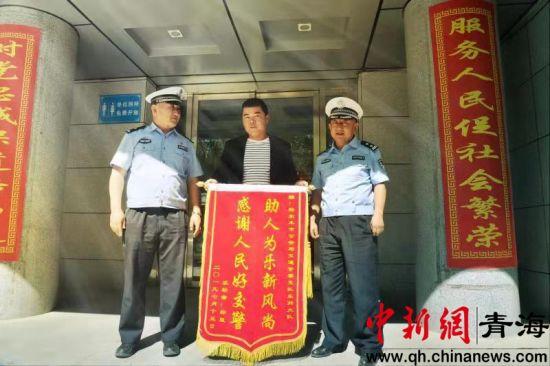 """为了感谢格尔木交警的及时救助,伤者家属特意制作了一面印有""""助人为乐新风尚,感谢人民好交警""""的锦旗,专程来到交警支队表示感谢。钟欣摄"""