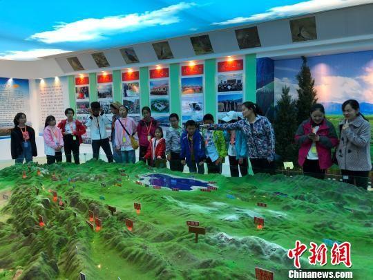 """图为祁连山国家公园青海片区开设的""""自然生态教育课""""现场,师生们了解祁连山地形沙盘。 钟欣 摄"""