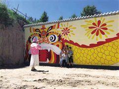 游客正在与峰堆乡的涂鸦作品合影