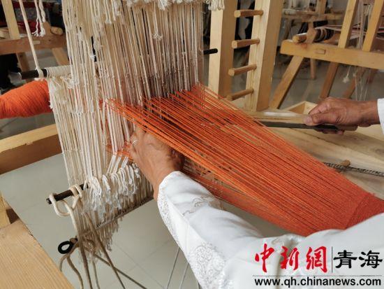 图为当地妇女正在纺织手工制品。李�S摄