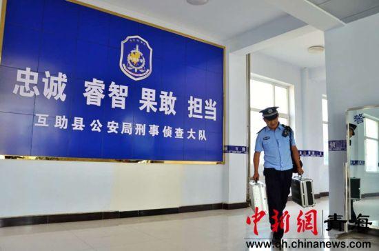 图为青海省海东市互助县公安局刑警大队侦查员李元寿拎着现场勘查工具箱、背着单反摄像机赶往案发现场。鲁丹阳摄