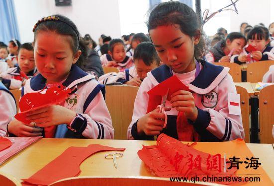 图为学生正在剪纸。