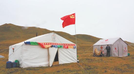 位于玛沁县拉加镇的安置点,党旗高高飘扬。 张浩 摄
