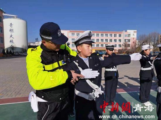 """图为执勤交警手把手教一位""""小交警""""如何当好文明交通志愿者。"""