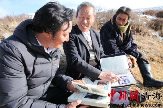 图为长寿(左二)老人向玛沁县下大武乡书记三智布(左一)介绍合作社成立的时的情景。厚厚的笔记本里详细记录了会议内容和图片。 胡贵龙摄
