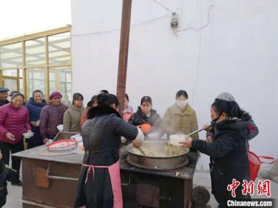 图为村里的老人们正在排队打饭。 史玉萍 摄