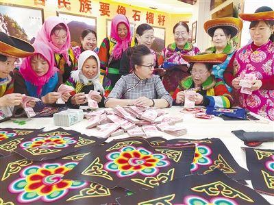 素隆姑公司在给绣娘分红。互助县扶贫开发局供图