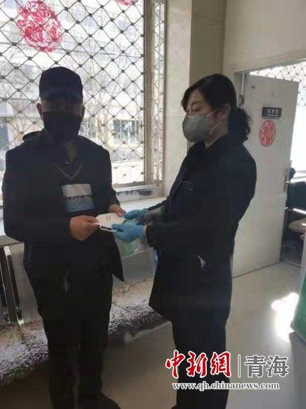 图为邮储银行青海省分行员工为前来营业网点的客户免费发放口罩。