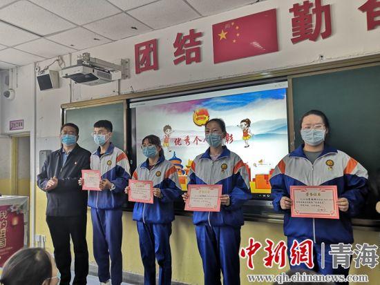 图为李天峰(左一)与受表彰的学生合影。潘雨洁摄