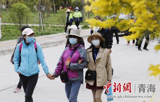 图为:游客在青海省同仁县参与徒步运动。