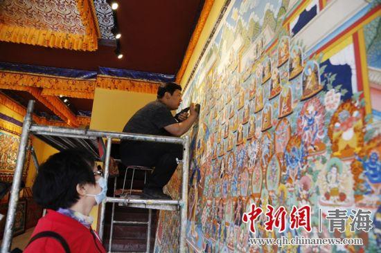 图为:游客在活动中参观了解大型热贡唐卡绘制过程。