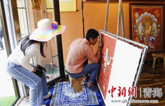 图为:游客在活动中参观了解热贡唐卡绘制过程。